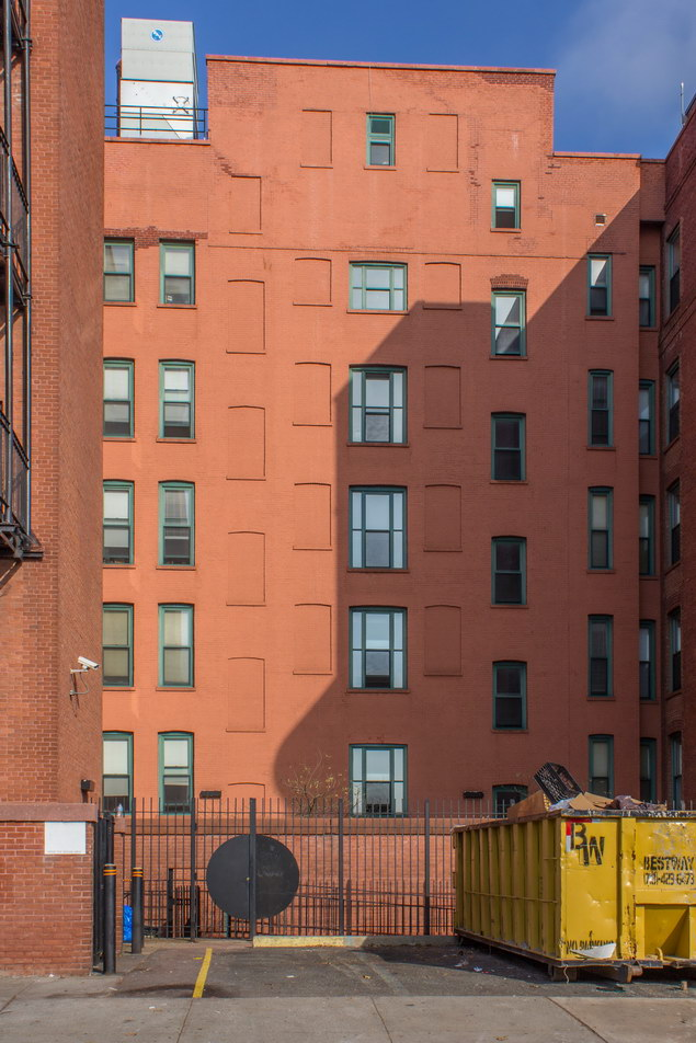 A one-story brick wall hides a garden courtyard.
