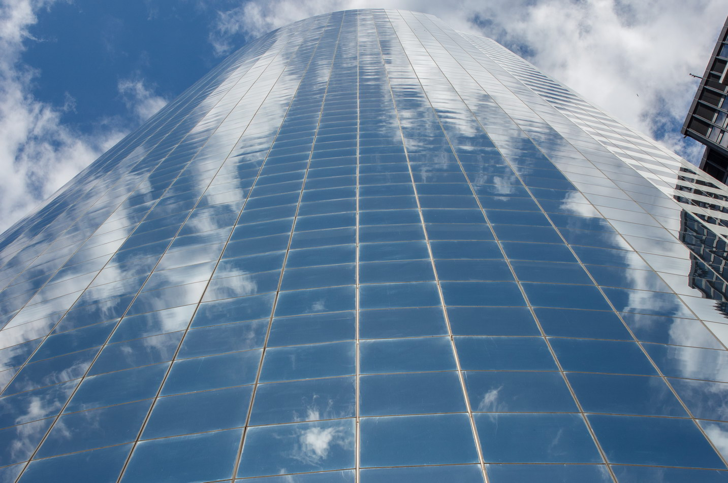 The curved glass facade reflects the sky.