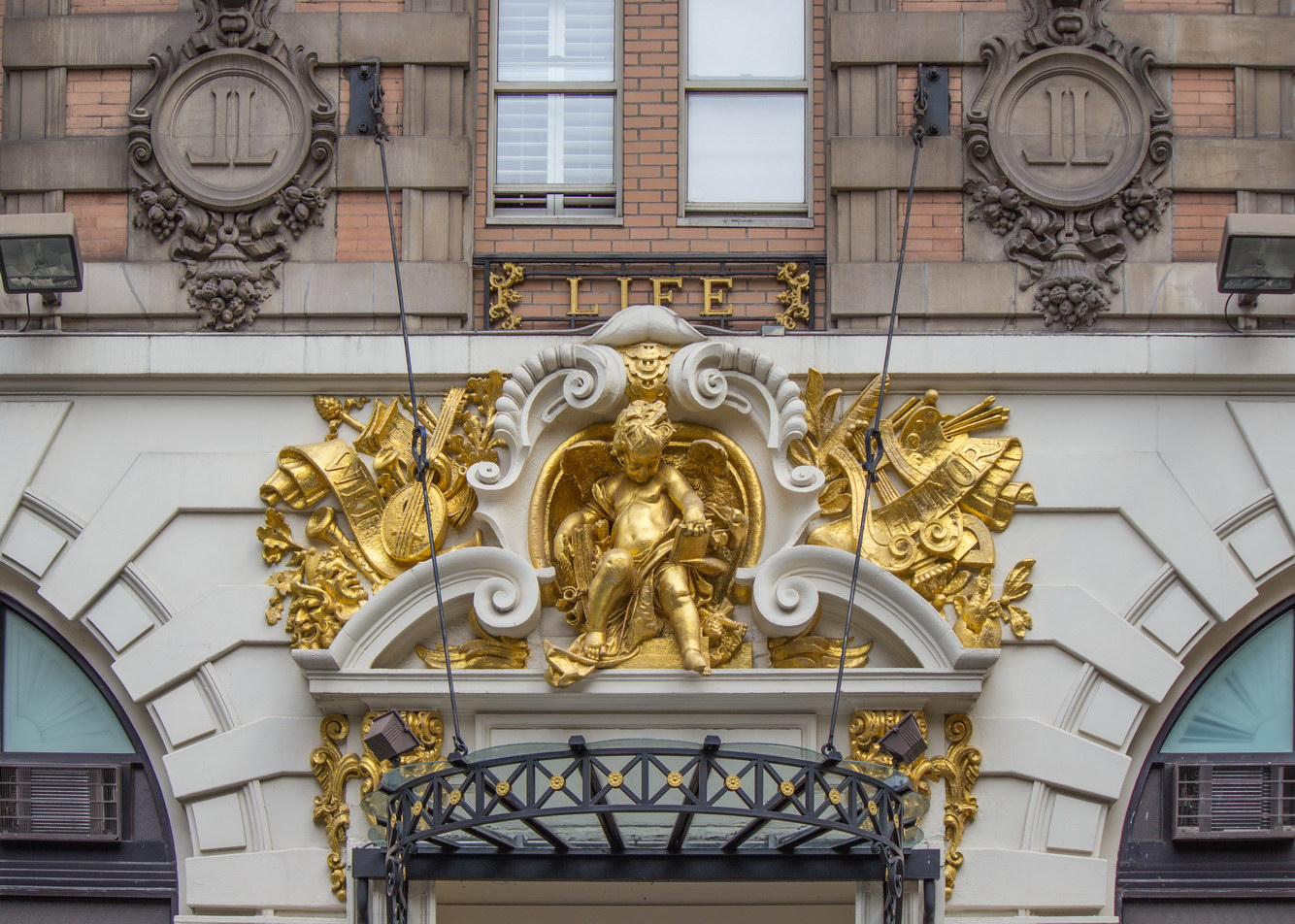 """The gilding was added by the hotelier.  You can make out """"WIT"""" and """"HUMOR"""" on the scroll."""