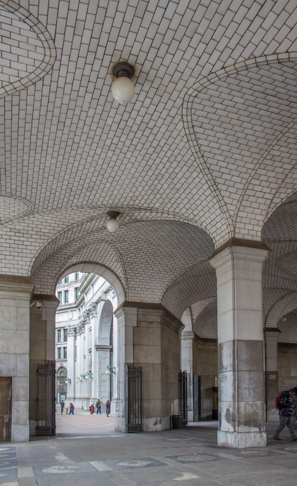 Under the south wing, a vaulted arcade shelters an entrance to the subway.